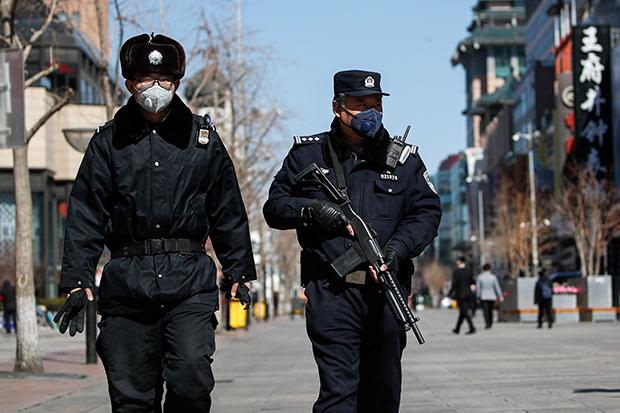 무장한 중국 공안들이 마스크를 쓰고 코로나19가 발생한 베이징의 한 상가를 순찰하고 있다.