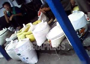 청진 시장에서 쌀을 팔고 있는 장사꾼들. 매대에 여러 종류의 곡식이 담긴 자루가 놓여 있고 가격표도 보인다.