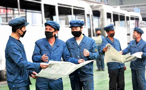 평양무궤도전차공장 근로자들이 마스크를 쓰고 평양종합병원 착공식에서 김정은 국무위원장 관련 내용이 실린 신문을 읽고 있다.