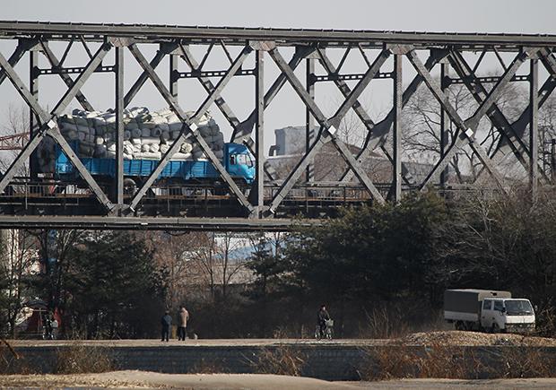 중국 단둥과 북한 신의주를 연결하는 다리 위를 화물을 가득 실은 트럭이 달리고 있다.