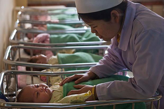 평양산원의 한 간호사가 신생아실에서 갓난 아기들을 돌보고 있다.