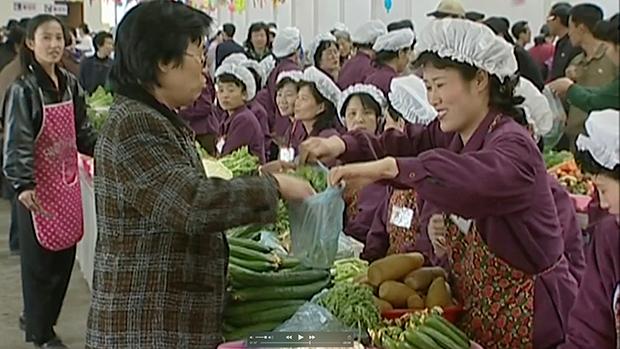 평양의 통일거리시장에서 시민들이 야채를 사고 있다.