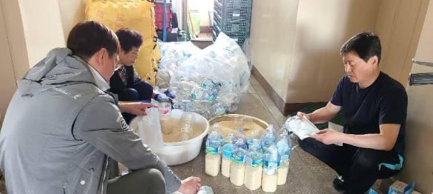 사단법인 큰샘 회원들이 23일에 있을 100회차 활동을 위해 쌀과 마스크를 페트병에 담고있다.