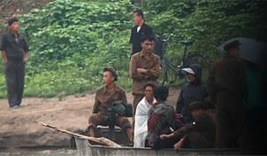 중국과 북한의 접경지역인 압록강변에서 북한 군인과 주민들이 배를 타고 압록강을 건너고 있다.