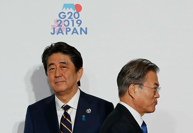 문재인 대통령이 지난달 말 인텍스 오사카에서 열린 G20 정상회의 공식환영식에서 의장국인 일본 아베 신조 총리와 악수한 뒤 행사장으로 향하고 있다.