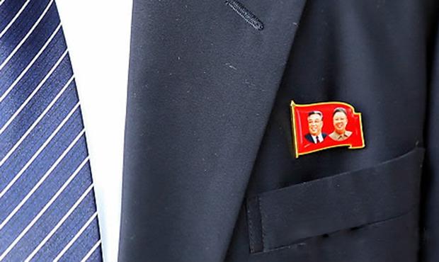 북측 경호원 왼쪽가슴에 김일성 주석·김정일 국방위원장의 사진이 새겨진 배지가 달려 있다.