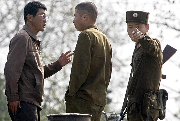 신의주 강변에서 북한군 병사가 어딘가를 보며 손짓을 하고 있다.