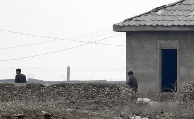 중국 랴오닝성 단둥 외곽에서 바라본 북한 국경지역에서 북한군 병사들이 막사에서 나오고 있다.