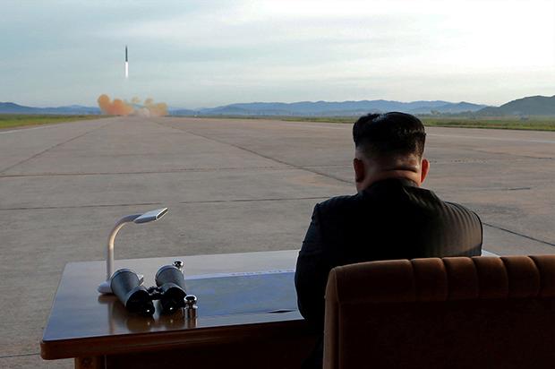 김정은 위원장이 중장거리전략탄도미사일 화성-12형 발사를 지켜보고 있다.