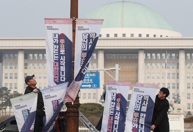 20일 여의도 국회의사당 앞 가로등에 서울시선거관리위원회 직원들이 '내가 만드는 대한민국, 투표로 시작됩니다' 등의 문구가 적힌 현수기를 게시하고 있다.