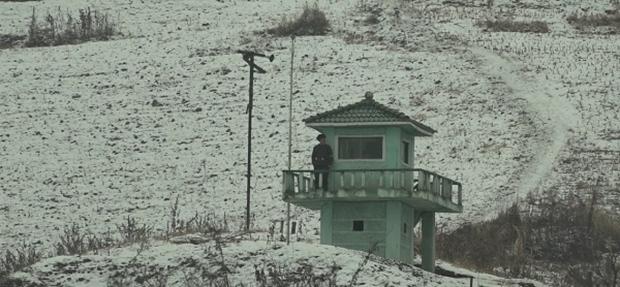 북한 국경도시의 한 경비병이 보초를 서고 있다.