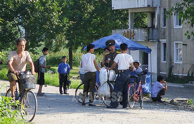 농촌에서 구매한 곡물을 운반하던 도중 보안원의 단속에 걸린 부부.