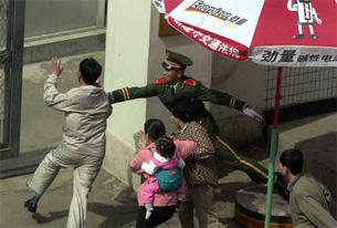 2002년 5월 8일 김광철 씨(맨앞) 가족이 중국 심경 화평구의 일본대사관으로 경비원의 제지를 뚫고 들어가고 있다.