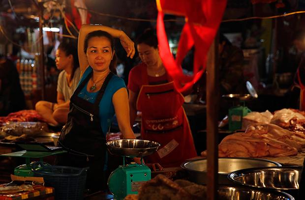 라오스의 한 여성이 시장에서 고기를 팔고 있다.