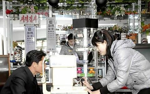 평양시 모란봉구역에 있는 평양안경점에서 근로자들이 안경을 맞춰주고자 시력검사를 하고 있다.