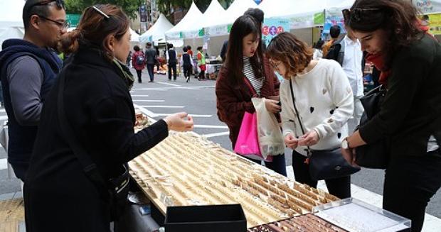 서울 중구 무교로에서 열린 서울 전통시장 한마당 축제에서 시민과 외국인 관광객이 상품을 고르고 있다.