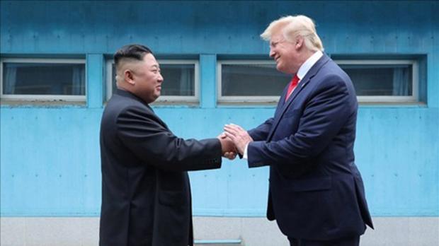 사진은 조선중앙통신이 홈페이지에 공개한 것으로, 군사분계선(MDL)을 사이에 두고 북미 정상이 손을 맞잡은 모습.