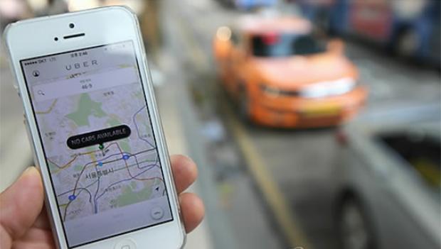 서울 시내의 한 택시 정류장을 배경으로 촬영한 휴대전화 상의 우버택시 애플리케이션.