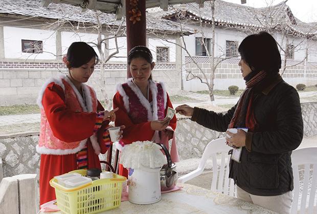 지난 2008년 남한 관광객이 개성에서 커피를 사며 1달러 짜리 지폐를 지불하고 있다.