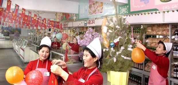 평양시 보통강구역에 있는 신원식료품상점에서 종업원들이 점내를 장식하고 있다.