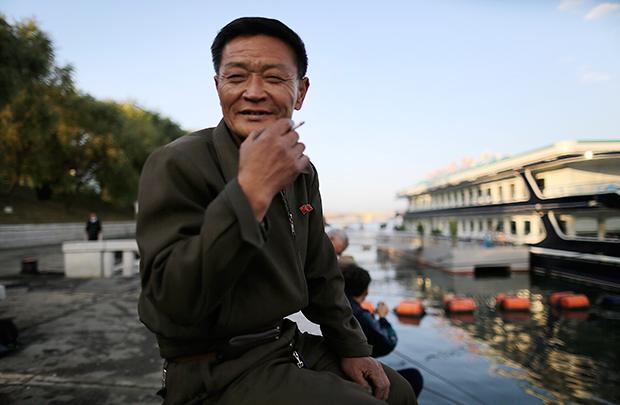 한 북한 주민이 대동강변에서 담배를 피우고 있다.