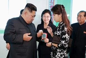 평양화장품 공장을 시찰 중인 김정은 위원장과 부인 리설주가 이 공장에서 생산한 화장품을 살펴보고 있다.