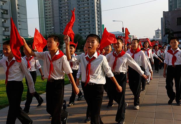 북한 학생들이 노래를 부르며 평양 시내를 행진하고 있다.