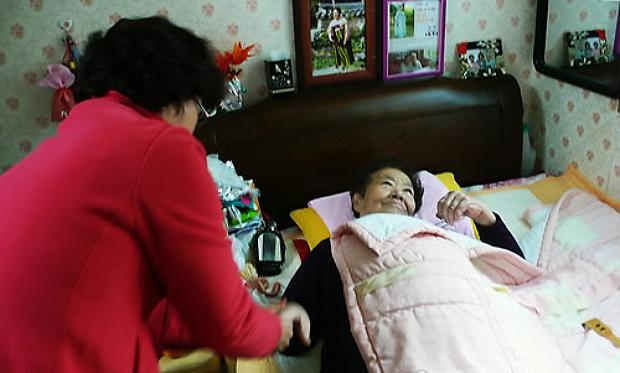 거동이 불편한 할머니의 팔을 요양사가 안마해주고 있다.